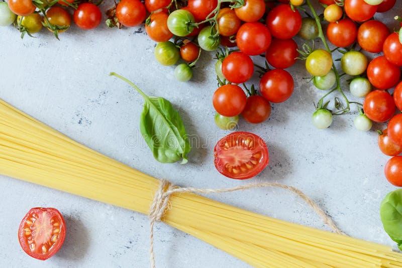 食物框架 面团成份概念 未煮过的意粉和西红柿与绿色蓬蒿在蓝色背景 顶视图 免版税库存图片