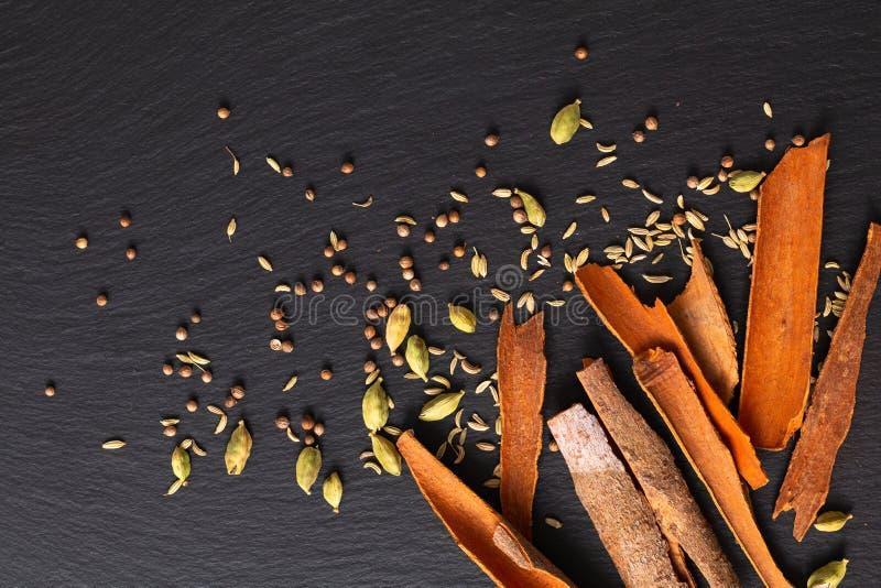 食物概念分类东方人加香料豆蔻果实荚、芫荽子、茴香和桂香在黑板岩的桂皮棍子 库存图片