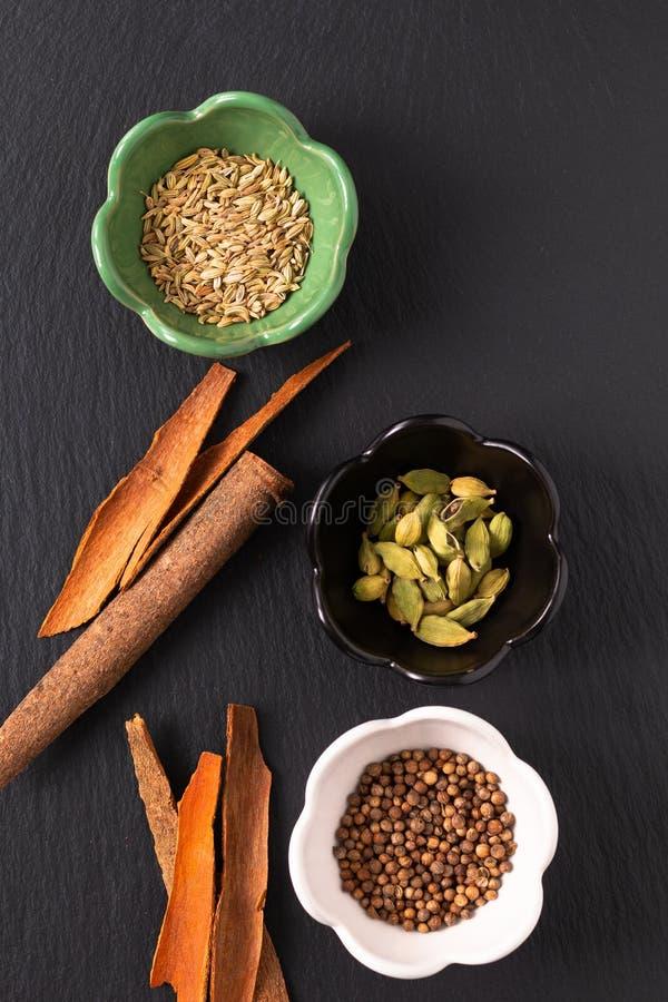 食物概念分类东方人加香料豆蔻果实荚,芫荽子,茴香,并且桂香桂皮在黑板岩的棍子 库存图片