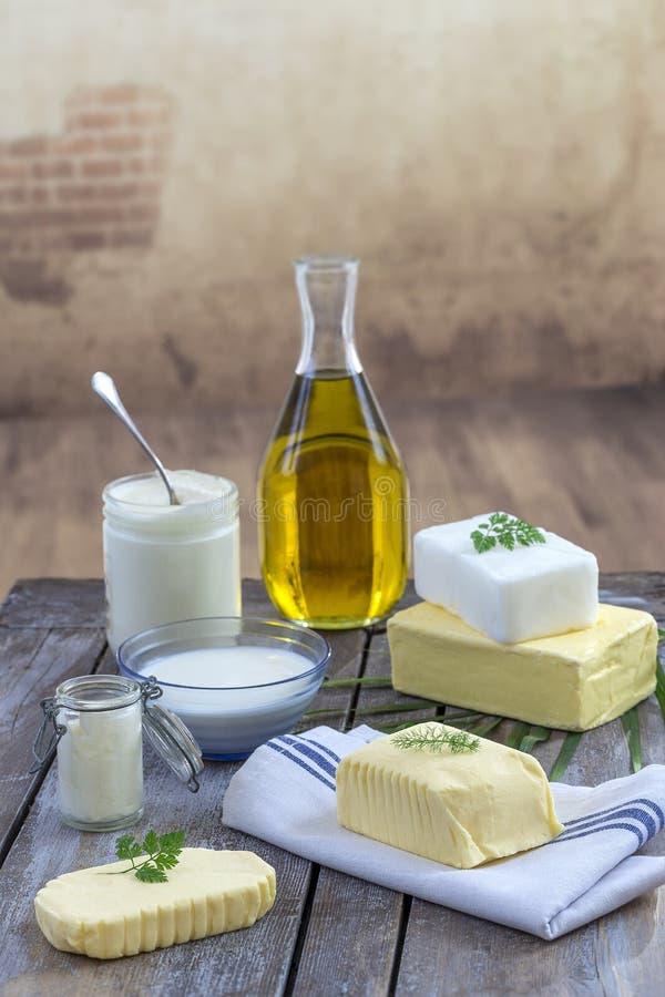食物油脂和油:套乳制品和油和脂肪在木背景 库存图片