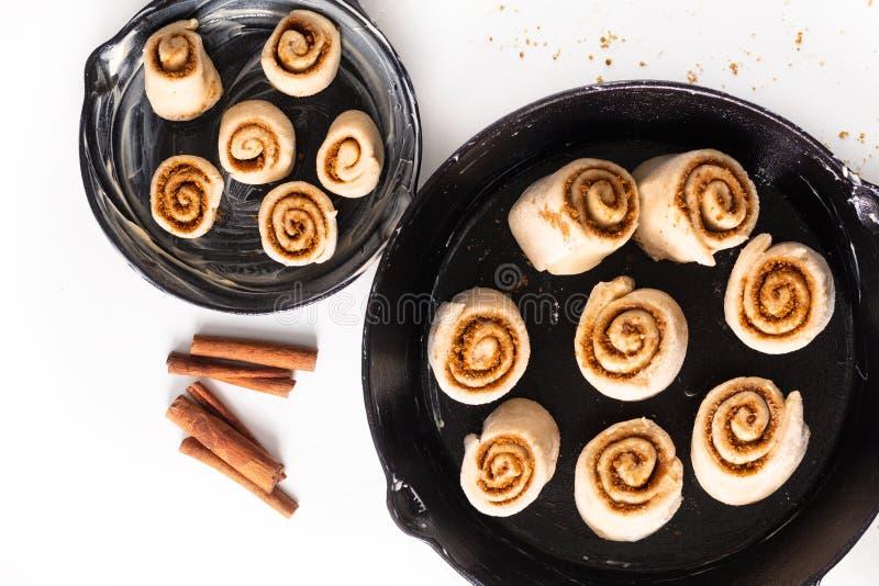 食物烘烤的概念面包店准备证明了桂皮卷的面团在长柄浅锅在白色背景的铁平底锅 免版税库存照片