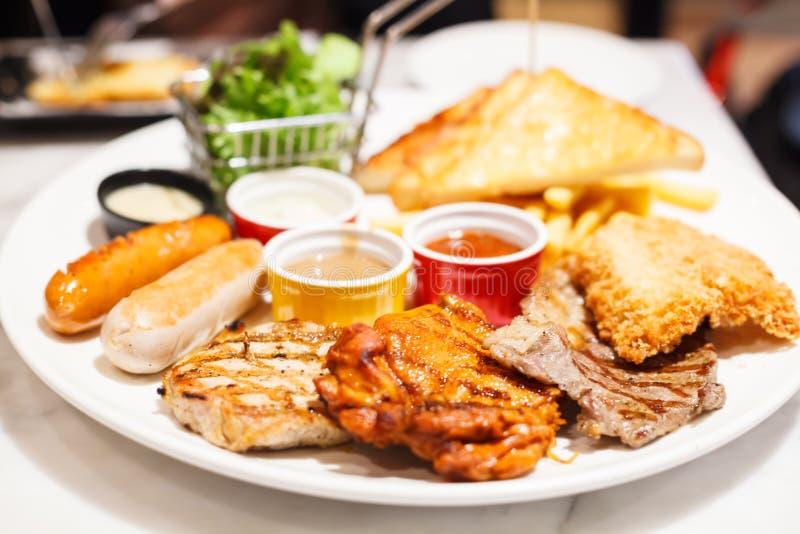 食物牛排和香肠分类辣鸡,猪肉,牛肉,鱼服务与法国油煎,并且被烘烤的面包,支持与 图库摄影