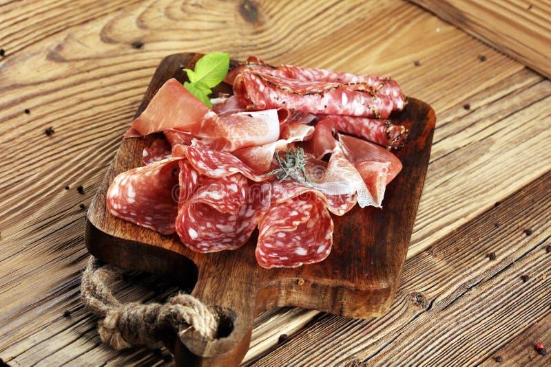 食物盘子用可口蒜味咸腊肠、未加工的火腿和意大利crudo或者ja 库存图片