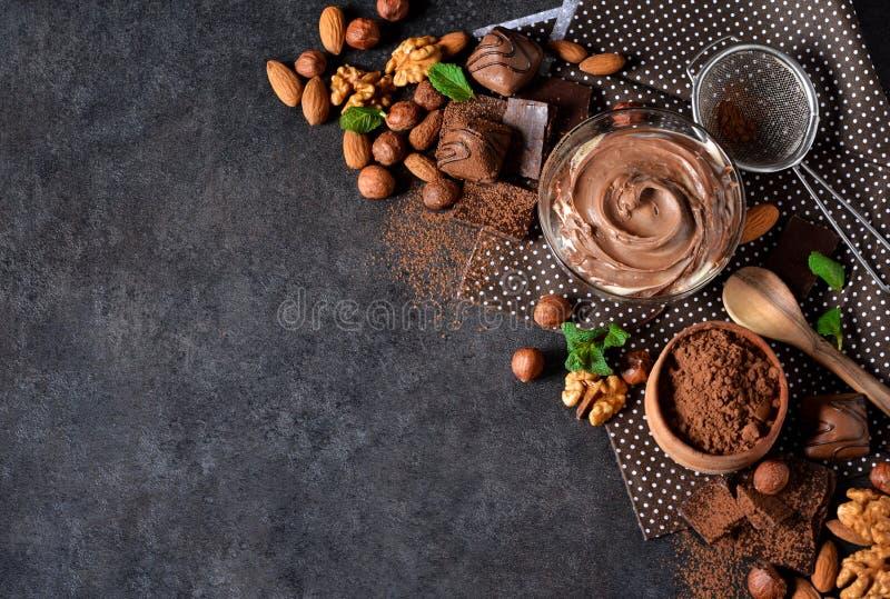 黑食物背景用可可粉、坚果和巧克力 免版税库存图片