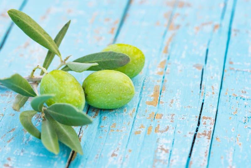 食物背景用在早午餐的新鲜的绿橄榄在土气蓝色木桌上 免版税库存图片