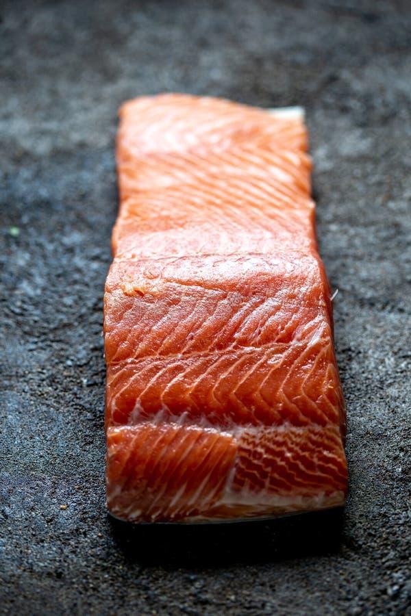 食物背景用新鲜的三文鱼里脊肉牛排、柠檬和香菜 库存照片