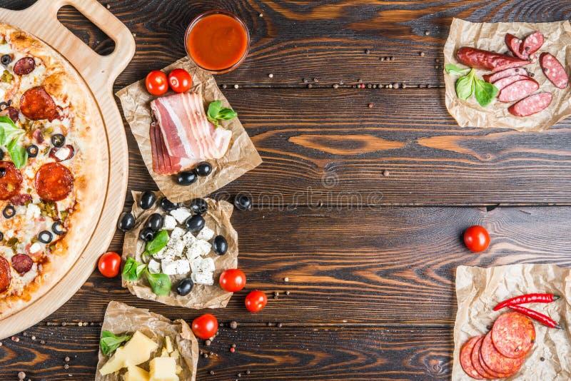 食物背景设计 蒜味咸腊肠,意大利辣味香肠,烟肉,乳酪,樱桃 免版税库存图片