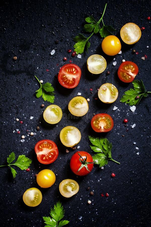 食物背景:红色,黄色和橙色西红柿,黑b 免版税库存图片