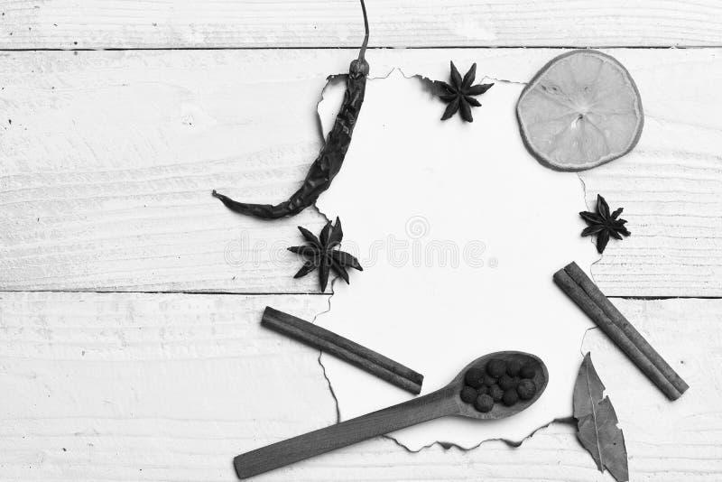 食物艺术概念 套在米黄木背景的干香料 调味品的构成在纸片断的 捞出木头 免版税库存图片
