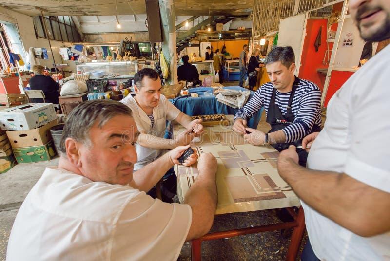 食物获得乐趣在断裂期间和打棋-多米诺的市场工作者 免版税库存图片
