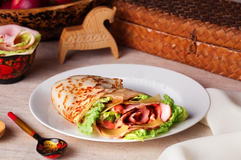 食物薄煎饼火腿乳酪莴苣和调味汁在板材静物画 免版税图库摄影