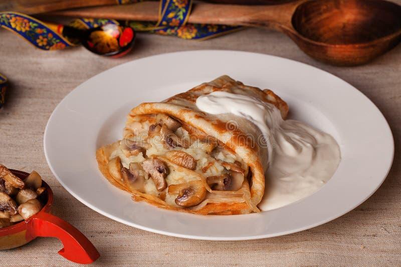 食物薄煎饼用蘑菇和酸性稀奶油在静物画农村土气 免版税库存照片