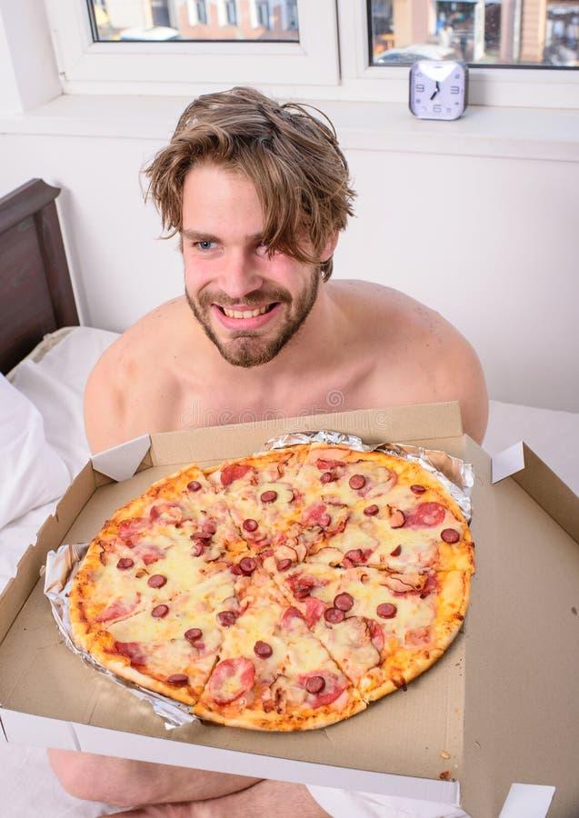 食物送货业务 供以人员吃低贱食物早餐的有胡子的英俊的学士在床上 人喜欢薄饼为 免版税库存图片