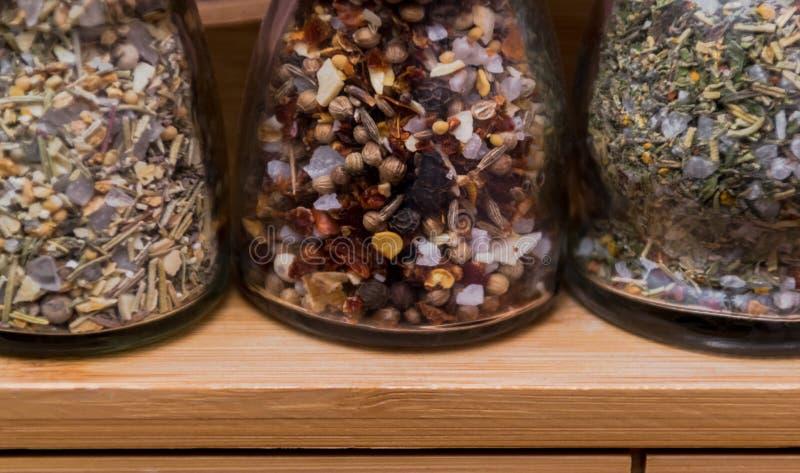食物配制概念;香料瓶的特写镜头图象在一个轻的木机架的 免版税库存照片