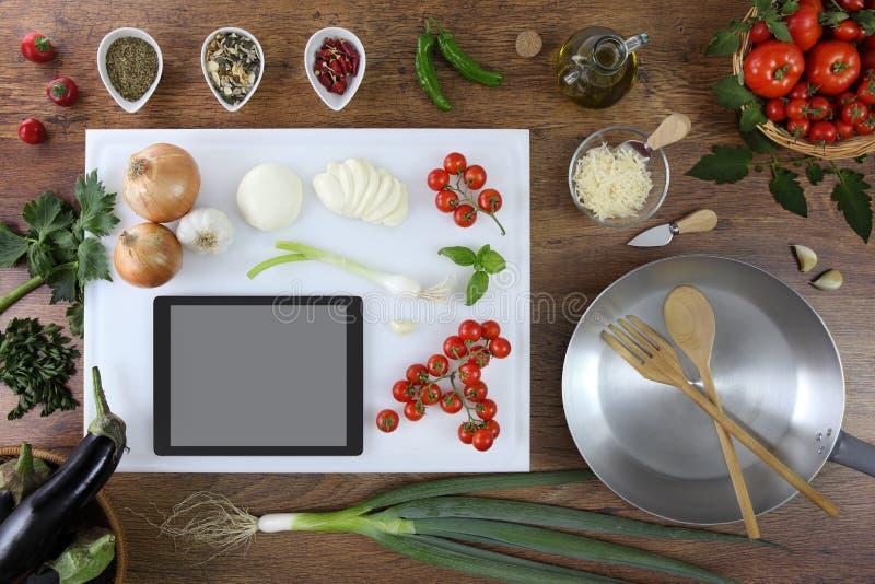 食物顶视图,在白色切板的数字式片剂在厨房里 免版税图库摄影