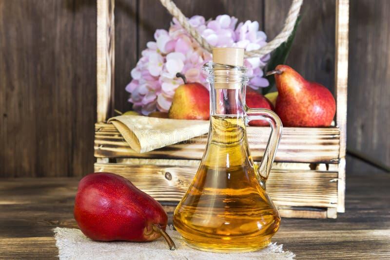 食物,素食主义,健康饮食食物,饮料 没有黏浆状物质的自然汁液从在一个玻璃蒸馏瓶的新鲜的红色梨,酒,利口酒 免版税库存照片