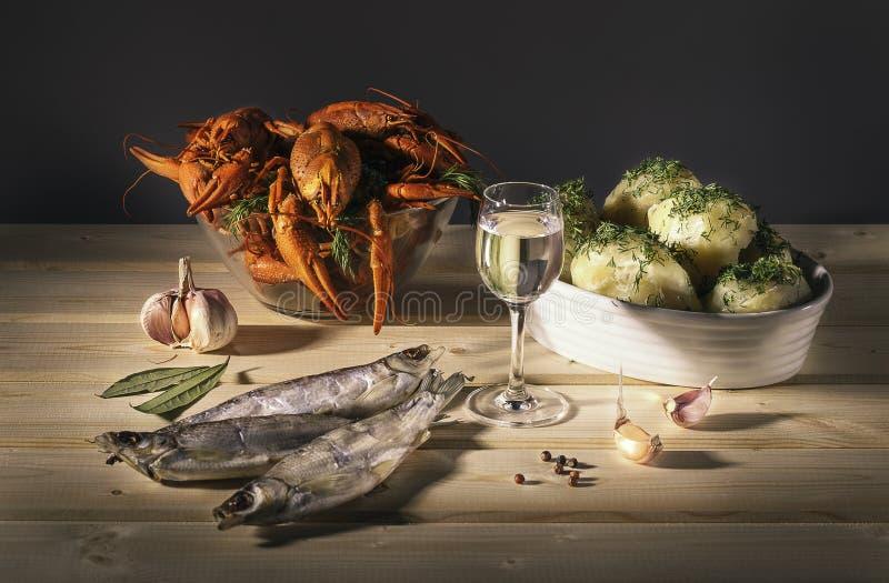 食物,艺术家 与小龙虾干燥鱼、伏特加酒和煮的土豆的静物画 免版税库存图片