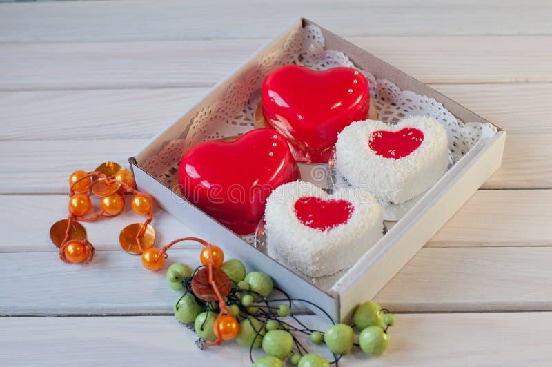 食物 在心脏形状的蛋糕在桌上的箱子在小珠附近 库存图片