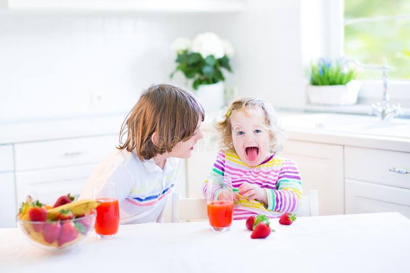 食用两个滑稽的孩子早餐饮用的汁的果子 免版税库存照片