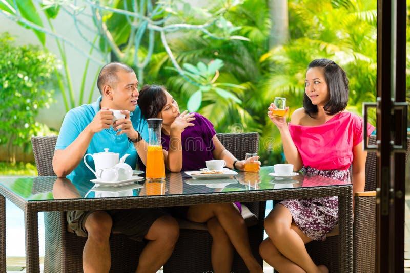 食用亚裔的朋友在家庭门廊的咖啡 免版税库存图片