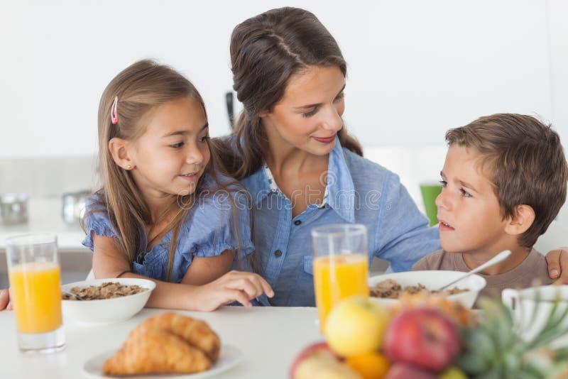 食用俏丽的母亲与她的孩子的早餐 图库摄影