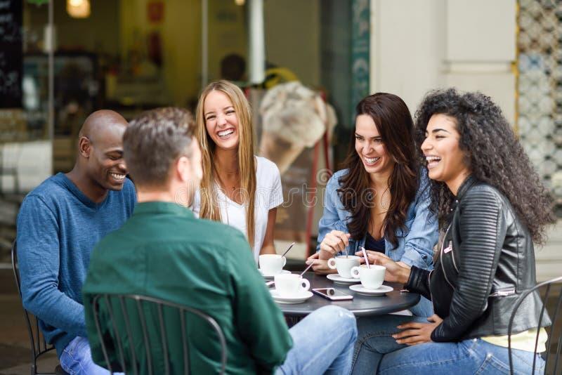食用多种族小组五个的朋友咖啡一起 免版税库存照片