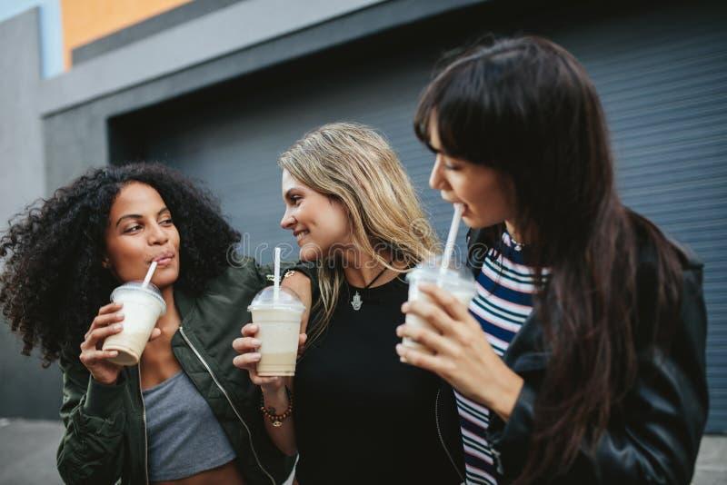 食用小组女性的朋友冰冻咖啡户外 图库摄影