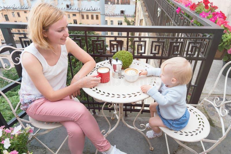 食用年轻愉快的母亲与婴孩的咖啡室外的阳台的 免版税库存照片