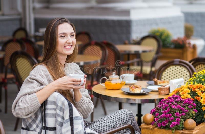 食用年轻时髦的妇女法国早餐用坐在咖啡馆大阳台的咖啡和蛋糕 免版税图库摄影
