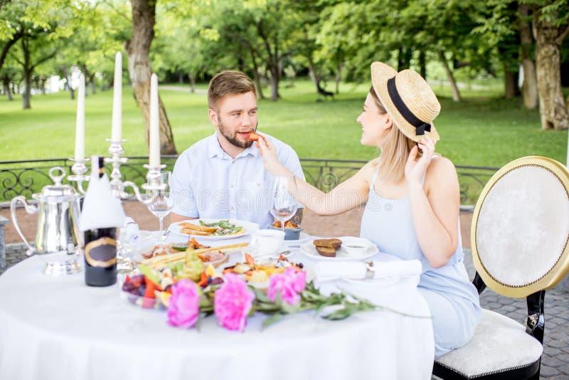食用年轻的夫妇浪漫早餐户外 库存照片