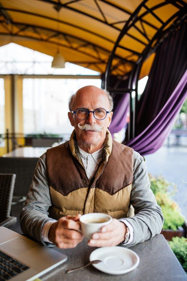 食用年长的人在咖啡馆大阳台的浓咖啡  免版税库存照片