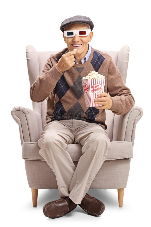 食用年长的人戴一个对3D眼镜和玉米花 免版税库存照片