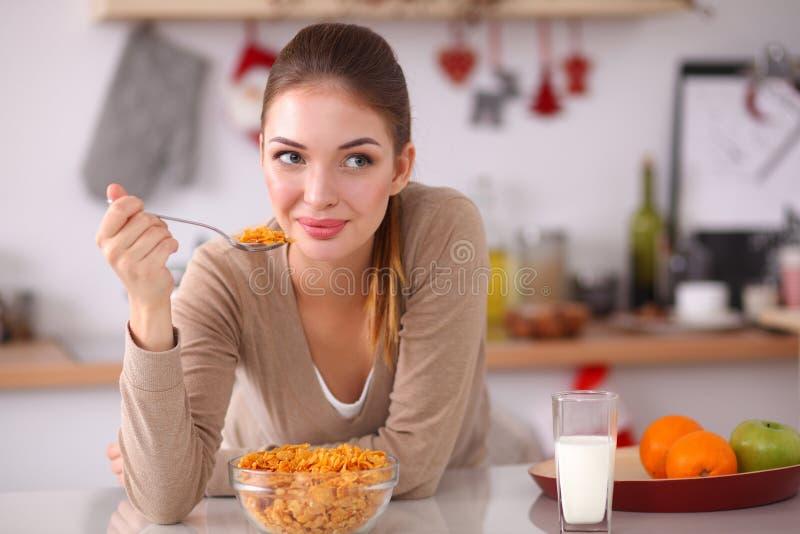 食用微笑的可爱的妇女早餐  图库摄影