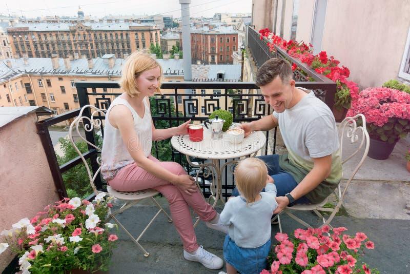 食用愉快的家庭在阳台的咖啡 免版税库存照片