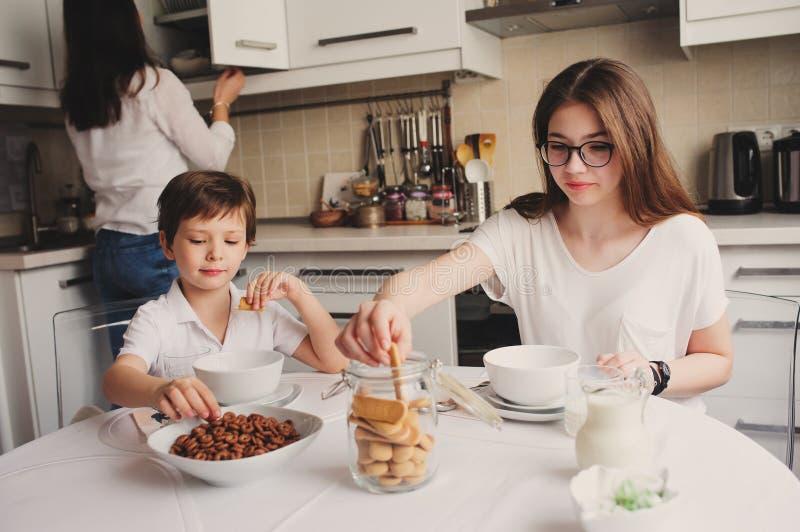 食用愉快的家庭早餐在家 有吃早晨的两个孩子的母亲在现代白色厨房里 库存照片