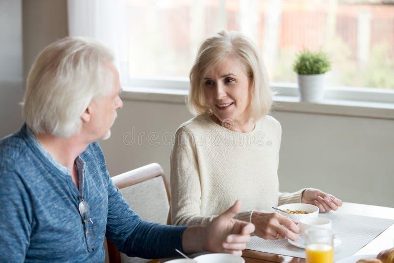 食用愉快的年迈的丈夫和妻子的谈话早餐在家 免版税库存照片
