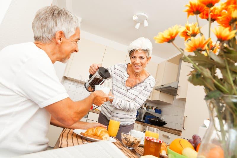 食用愉快的资深的夫妇早餐 免版税库存图片