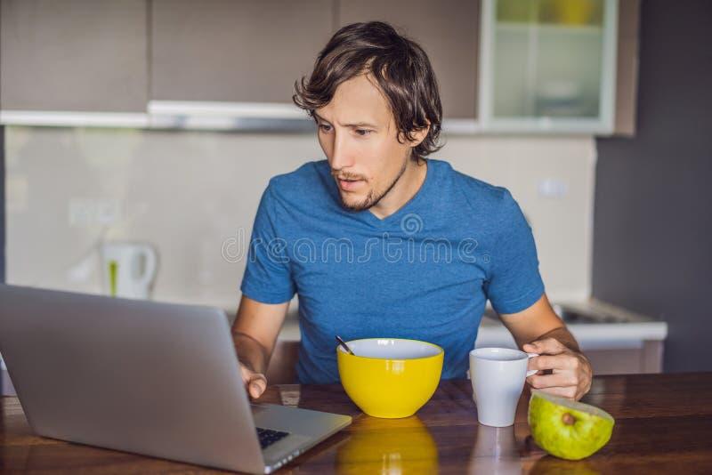 食用早餐和使用在厨房的年轻人膝上型计算机 免版税库存图片