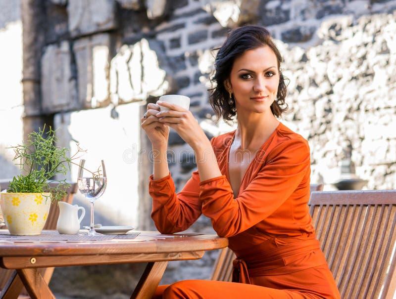 食用橙色的礼服的华美的迷人的女孩一杯咖啡外面 库存照片