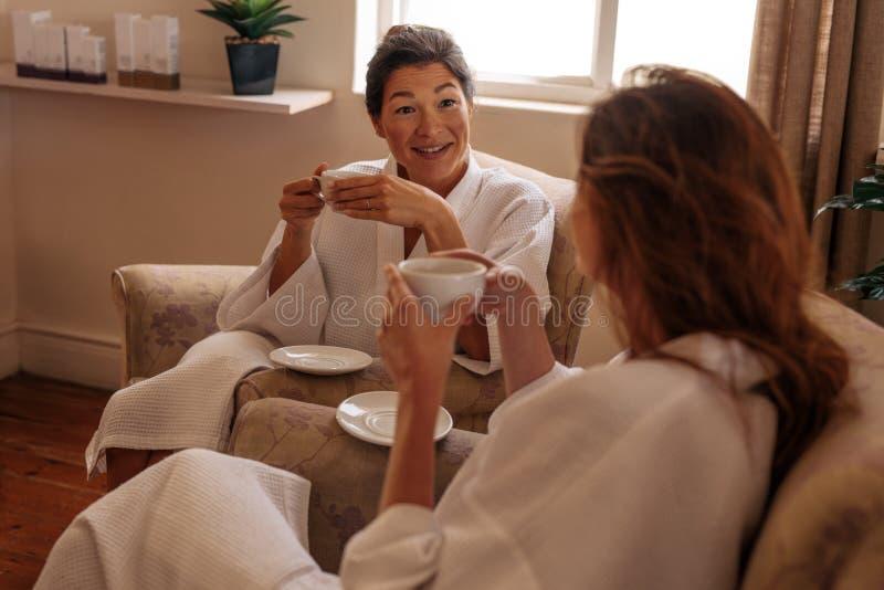 食用清凉茶和聊天在温泉的女性朋友 库存照片
