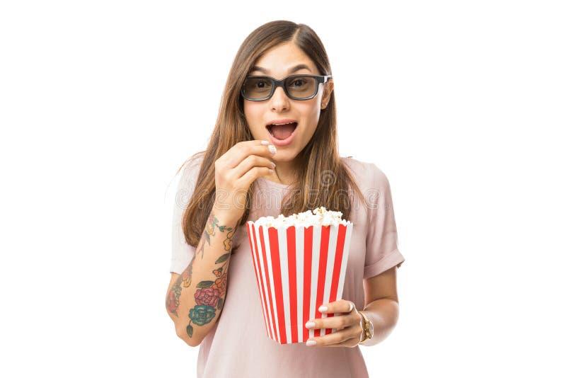 食用激动的妇女玉米花,当观看3D电影时 免版税库存照片