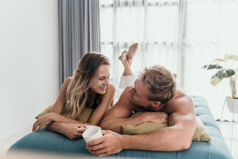食用的夫妇说谎在床上和一杯咖啡 免版税库存照片