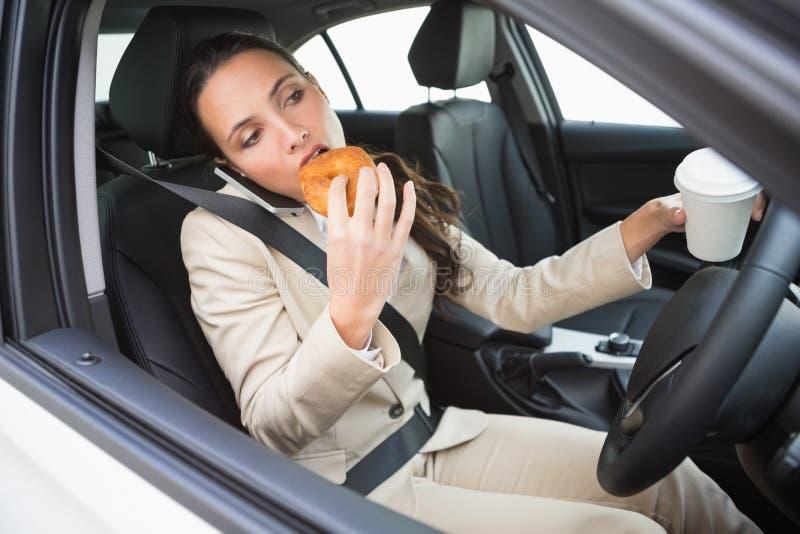 食用的女实业家咖啡和多福饼在电话 免版税库存图片