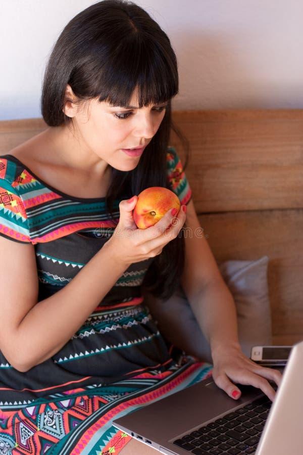 食用的少妇一顿健康快餐,当工作时 免版税库存图片
