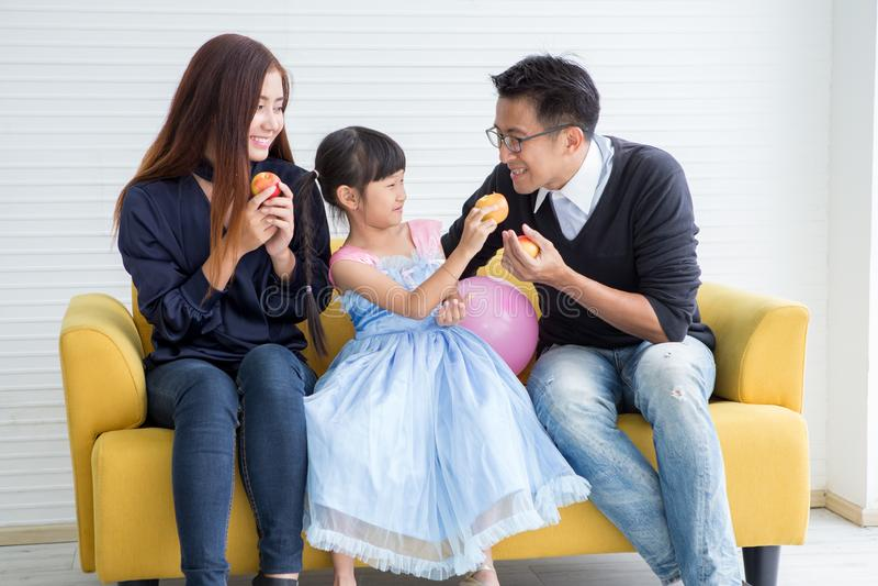 食用的幸福家庭和的孩子早餐坐吃苹果的沙发、母亲和父亲与女儿早晨一起 库存图片