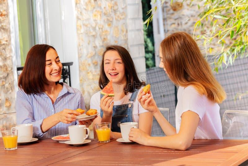 食用的幸福家庭在房子大阳台的早餐 图库摄影