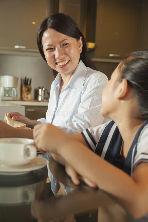 食用的母亲与她的女儿的早餐 免版税库存照片