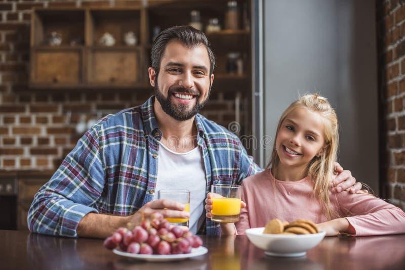 食用的父亲和逗人喜爱的女儿画象早餐一起 免版税库存照片