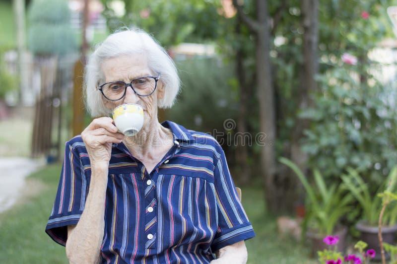 食用的老妇人一杯咖啡户外 免版税库存照片