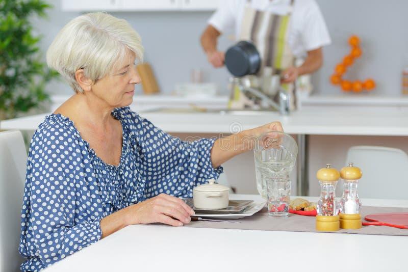 食用的老妇人在家早餐 库存照片